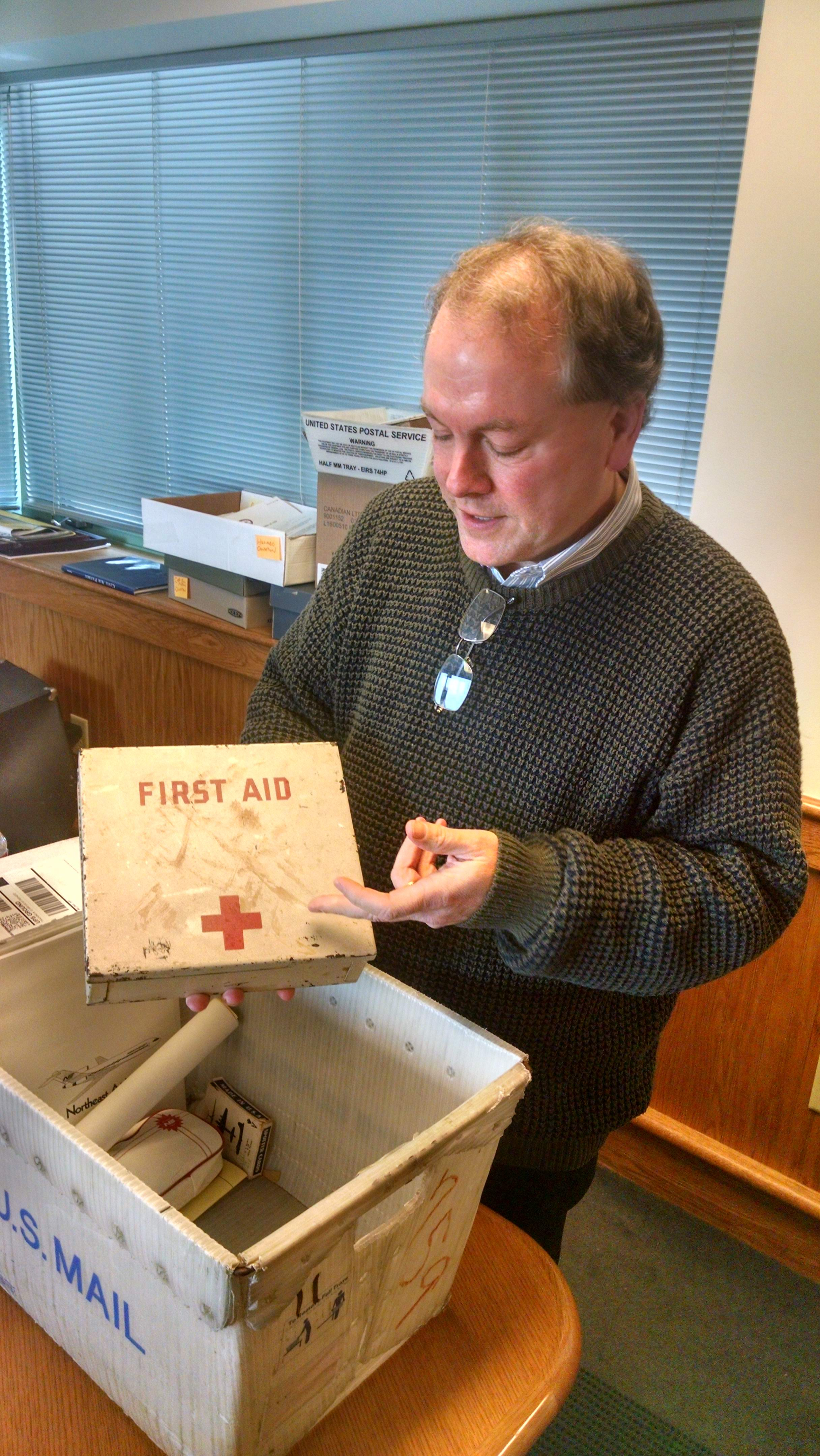 Aviation Museum Director Jeff Rapsis holds a First Aid kit from a DC3 that cdrashed on Mt. Success in 1954. Yes, that's blood on it.